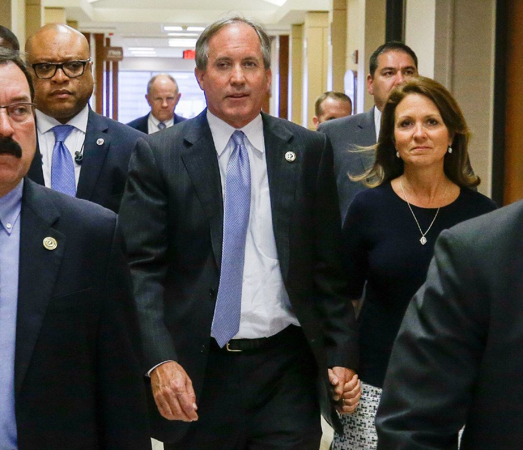 Republican Texas Attorney General Ken Paxton and his wife Angela Paxton, arrive for a hearing in the Harris County Criminal District Court in Houston, Thursday, July 27, 2017. A new trial date of Dec. 11 is set for Ken Paxton to face felony securities fraud charges. It's the third time a trial date has been set. (Melissa Phillip/Houston Chronicle via AP)