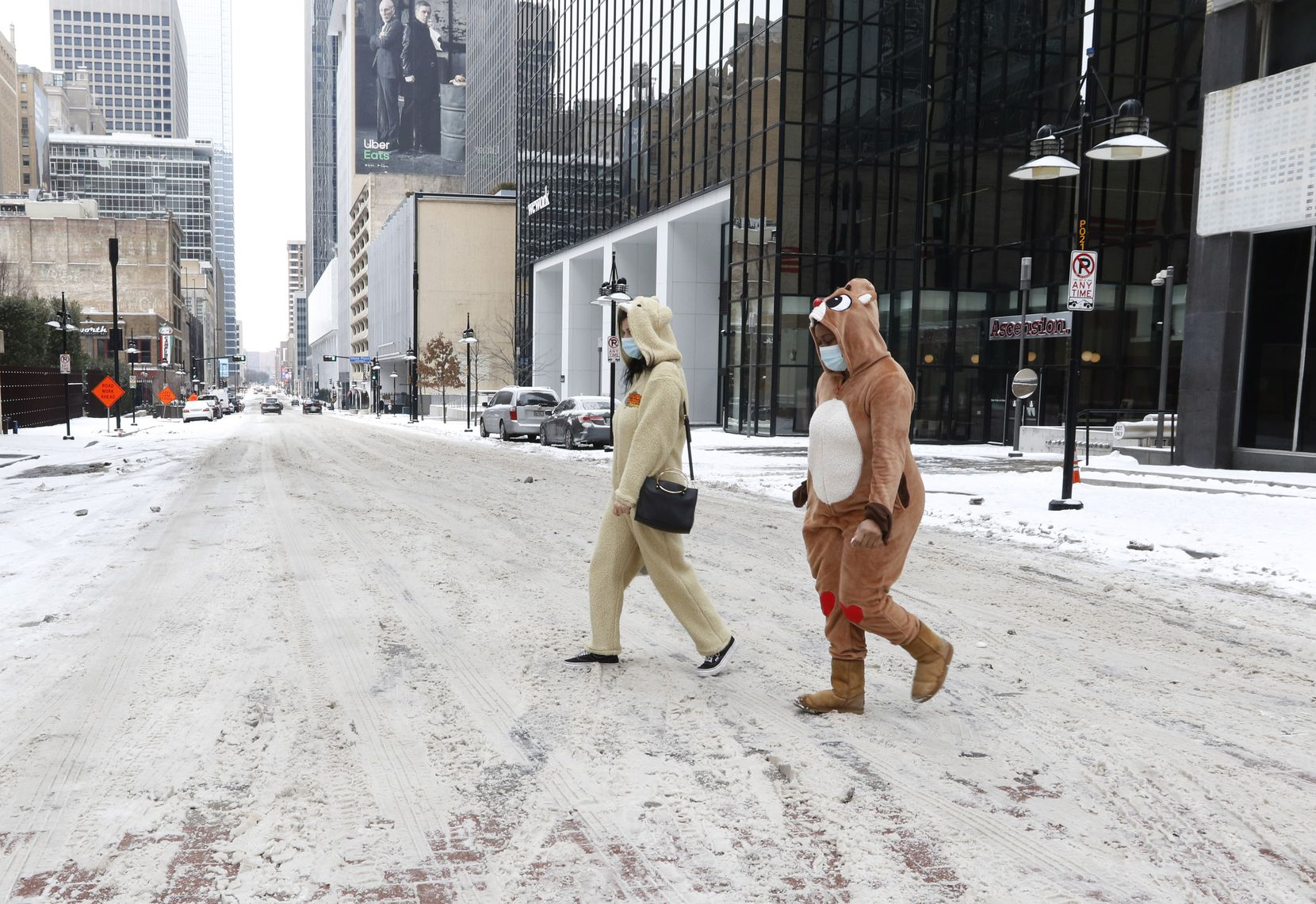 Leighanne Katz, left, dressed in a Thunder Buddies costume and Billian Lawal, right, in a Rudolph The Red-Nosed Reindeer costume walk from a 7-Eleven convenience store at the intersection of Elm St and Ervay St on Wednesday, February 17, 2021, in downtown Dallas.