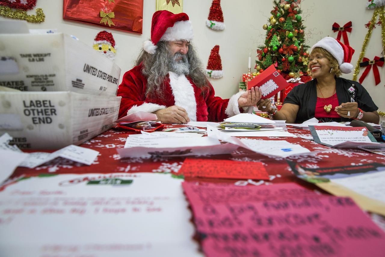 Adam Hamner y Linda Shelby, empleados del servicio postal, contestan las cartas para Santa Claus en el centro de distribución de la oficina de correo en Coppell. (DMN/SMILEY N. POOL)