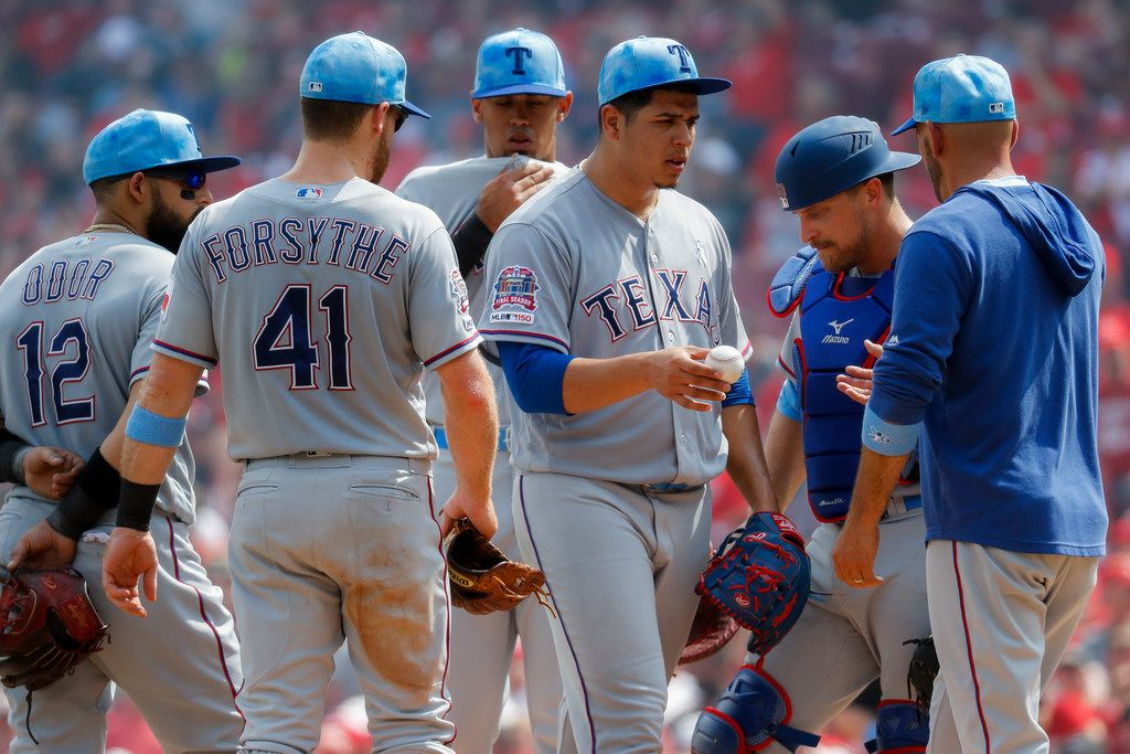 Texas Rangers starting pitcher Ariel Jurado, center right, is relieved by manager Chris Woodward in the fourth inning of a baseball game against the Cincinnati Reds, Sunday, June 16, 2019, in Cincinnati. (AP Photo/John Minchillo)