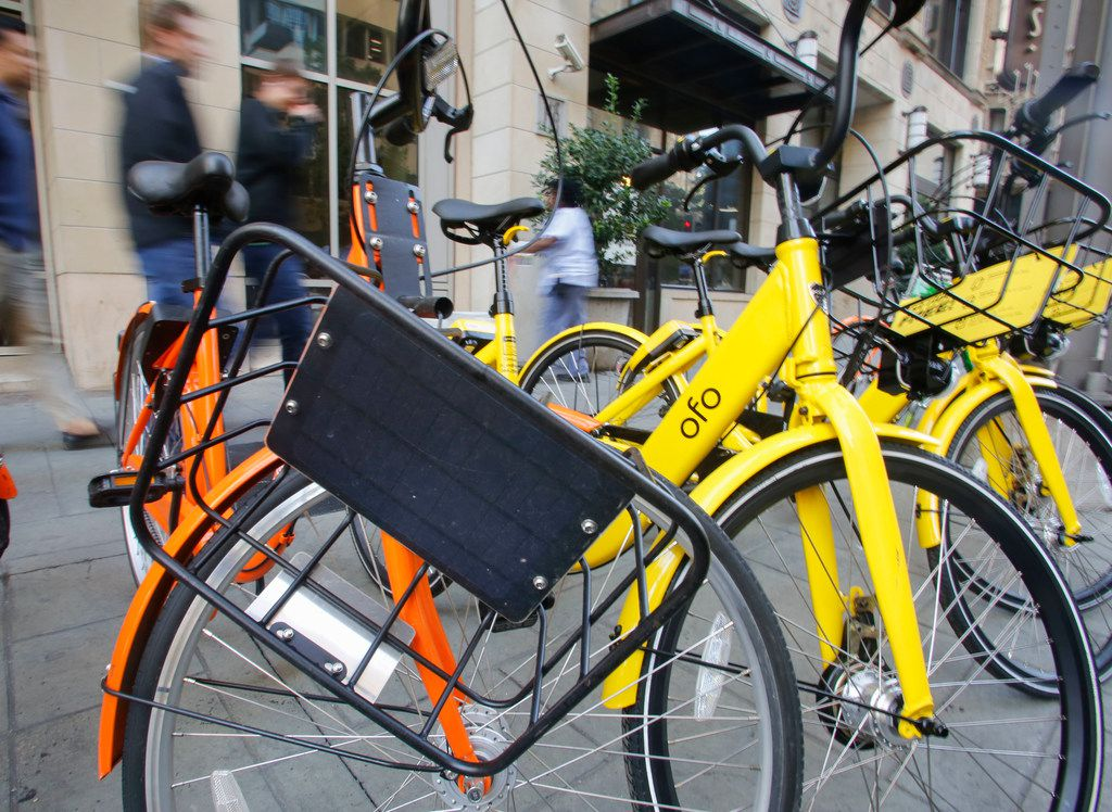 A damaged bike from Spin stands with bikes from other bike-share companies around downtown Dallas  Nov. 1. (Ron Baselice/The Dallas Morning News)