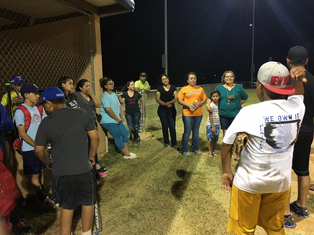 Carina Baeza, wearing an orange T-shirt, gathers with other mothers of players after practice to listen to the baseball team's coach.