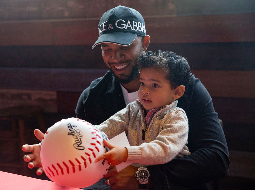 Texas Rangers shortstop Elvis Andrus (1) signs autographs while holding his son during the Rangers' Peek at the Park fanfest on Jan. 25, 2020 in Arlington. (Juan Figueroa/ The Dallas Morning News)