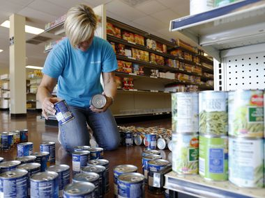A file photo shows Pam Eckerty coding soup cans at Frisco Family Services in Frisco. The organization is one that people can support during North Texas Giving Day.