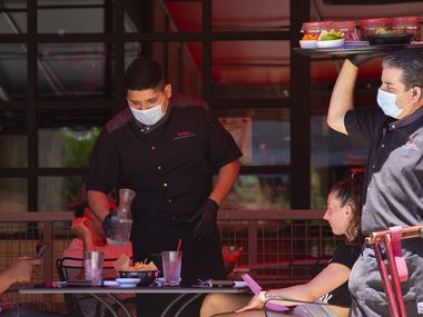 A server brings food out to the outside patio of Beto & Son at Trinity Groves on Friday in Dallas. Tables were spread out as restaurants are allowed to seat up to 25% of their total listed occupancy.
