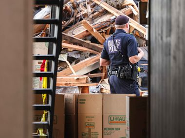 A Dallas police officer watches over the scene of Wednesday's explosion while residents wait to enter their units to gather belongings Friday, Oct. 1, 2021.