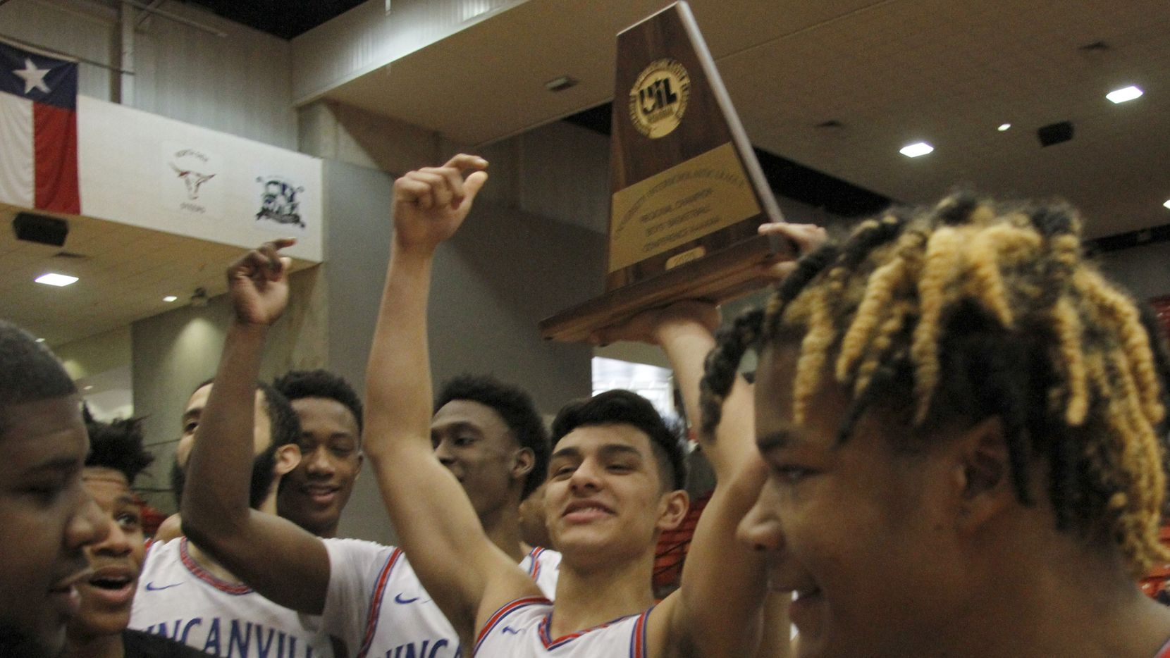 Duncanville guard Juan Reyna (1) raises the Class 6A Region 1 championship trophy as he celebrates with teammates following the Panthers' 59-43 victory over Odessa Permian to gain a berth in the UIL state tournament. The two teams played in the Class 6A Region 1 championship boys basketball playoff game at Wilkerson-Greines Activity Center in Fort Worth on March 7, 2020.