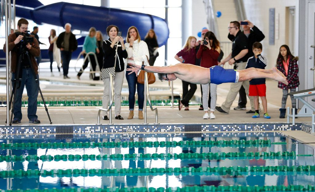 Former McKinney Mayor Brian Loughmiller took a ceremonial jump in the pool to swim a lap shortly after the ribbon cutting at the Apex Centre in this file photo from 2019. (Vernon Bryant/The Dallas Morning News)