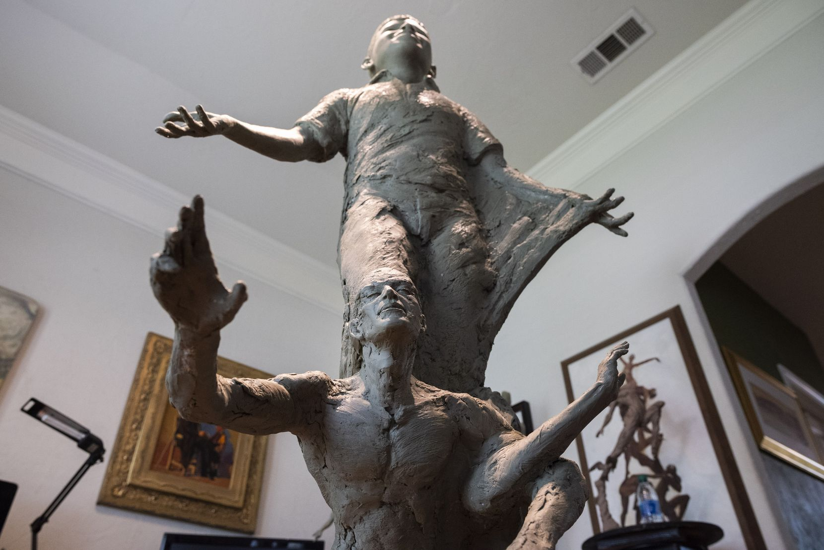 The details of fictional individuals at the base of the statue show people with interlocked arms or reaching for others in the statue depicting Santos Rodriguez, at the studio of sculptor Seth Vandable in Cedar Hill, on Tuesday, July 20, 2021.