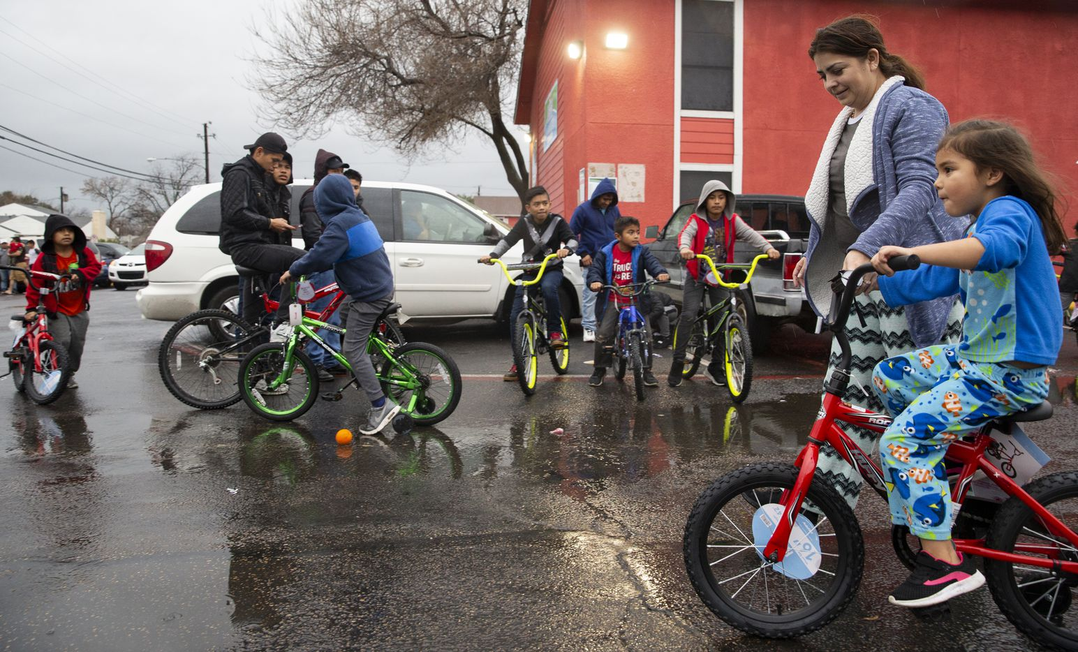 Families and children tried out new bikes they received from Israel Alonso, a local faith leader and volunteer with S.O.U.L. ministries on Dec. 28, 2019, in Dallas. With the help of Jennifer and Leon Birdd, Alonso helped provide his community with the bikes and food.