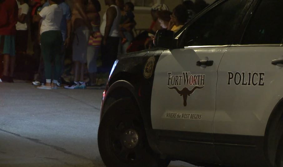 A crowd gathers outside a home where a man was shot to death Monday night in Fort Worth.