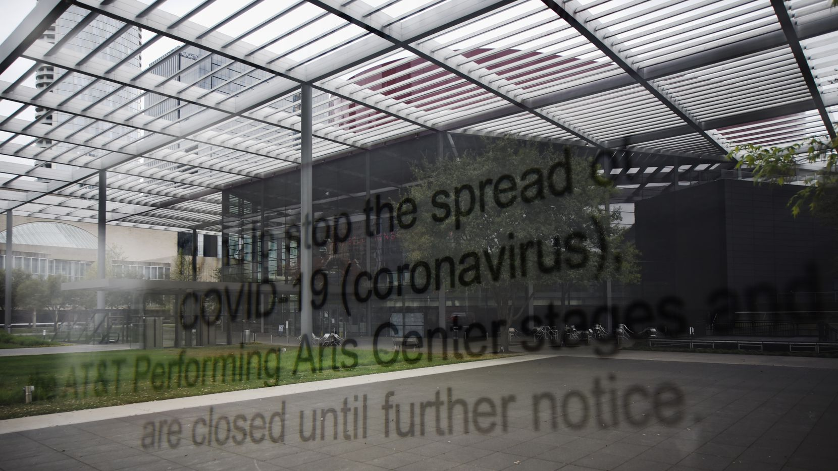A double exposure image shows the Winspear Opera House, a dried reflecting pool at Sammons Park and signage stating that all buildings at the AT&T Performing Arts Center complex are closed due to COVID-19, Saturday afternoon March 21, 2020 in Dallas.