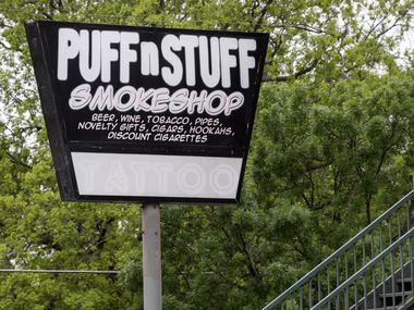 A sign for Puff n Stuff, a smoke shop which received a cease and desist order from the City of Dallas for violating coronavirus related restrictions, stands along Columbia Avenue, Friday, April 17, 2020 in Dallas. Store owners responded with a lawsuit, arguing that they are exempt under the bodega category because they sell groceries and other essential sundries. (Jeffrey McWhorter/Special Contributor)