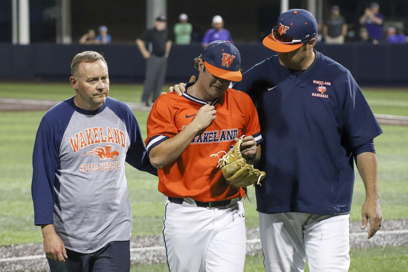 Frisco Wakeland pitcher Robert Fortenberry (9) is comforted after exiting the game because of an injury during game two of the UIL baseball 5A Region II final series against Hallsville at Horner Ballpark in Dallas on Friday, June 4, 2021. (Elias Valverde II / Special Contributor)