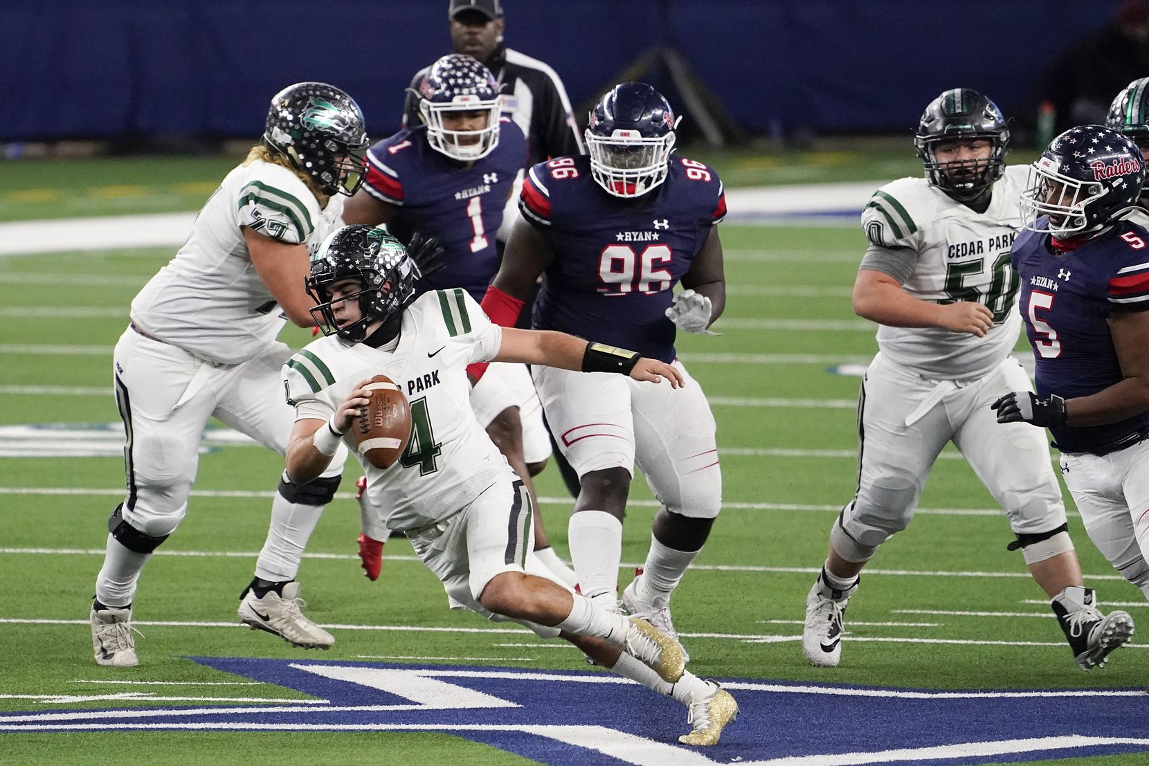 Cedar Park quarterback Ryder Hernandez (4) is flushed from the pocket by Denton Ryan defensive lineman Bear Alexander (96) during the second half of the Class 5A Division I state football championship game at AT&T Stadium on Friday, Jan. 15, 2021, in Arlington, Texas. Ryan won the game 59-14. (Smiley N. Pool/The Dallas Morning News)