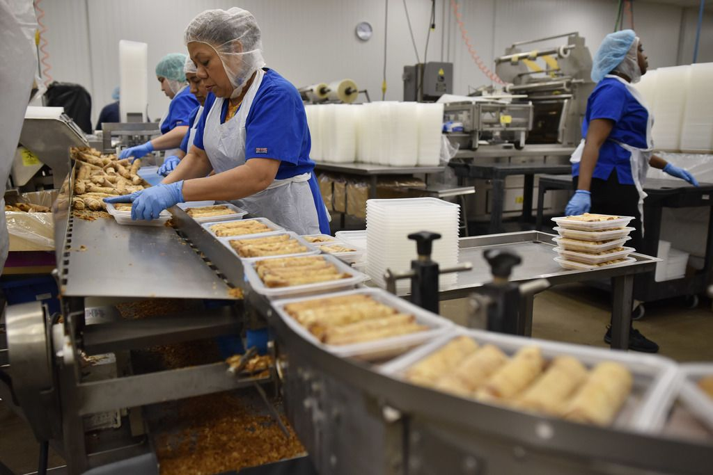 Employees of Van's Kitchen package egg rolls at the Van's Kitchen production plant.