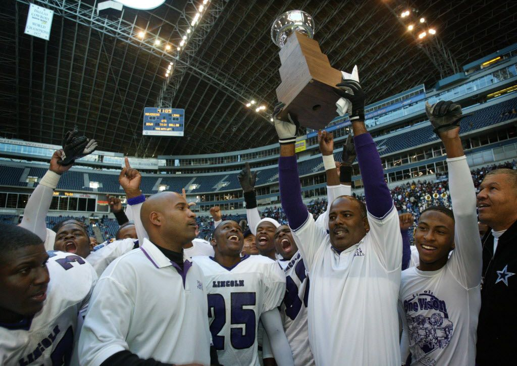 Dallas Lincoln High coach Reginald Samples  (with trophy) and assistants and team members celebrate after the Tigers 21 -7 victory in the Class 4A Division II State Semifinal Championship at Texas Stadium. Lincoln would lose in the state title game the following game.