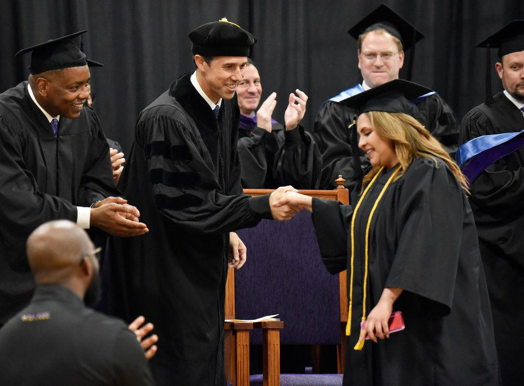 Presidential candidate Beto O'Rourke (center) shakes the hand of co-valedictorian Lorenza Najera during Paul Quinn College's commencement convocation on Saturday, May 4, 2019. At the left is Plano Mayor Harry LaRosiliere.
