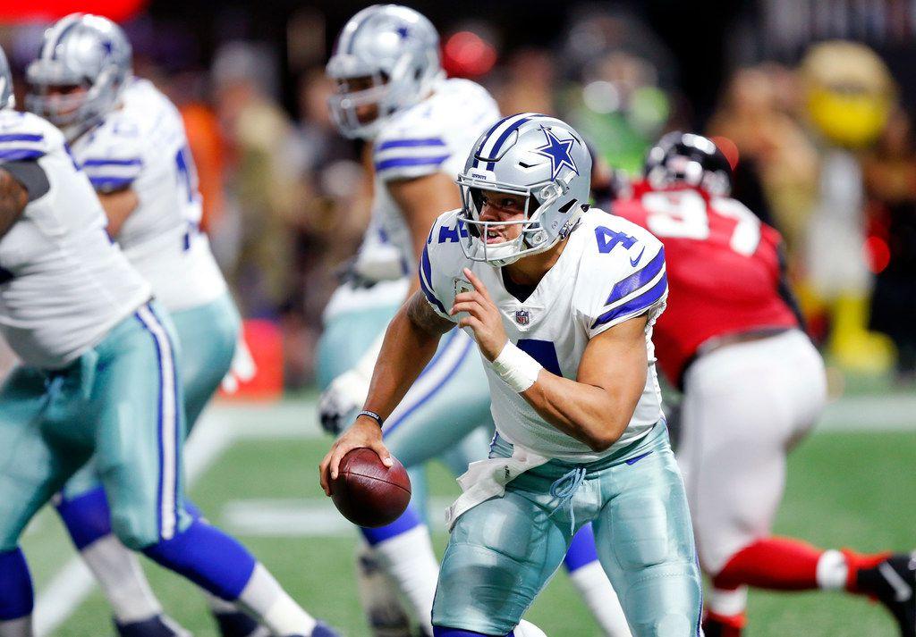 Dallas Cowboys quarterback Dak Prescott (4) rushes with the ball in the second quarter against the Atlanta Falcons at Mercedes-Benz Stadium in Atlanta, Georgia, Sunday, November 12, 2017.