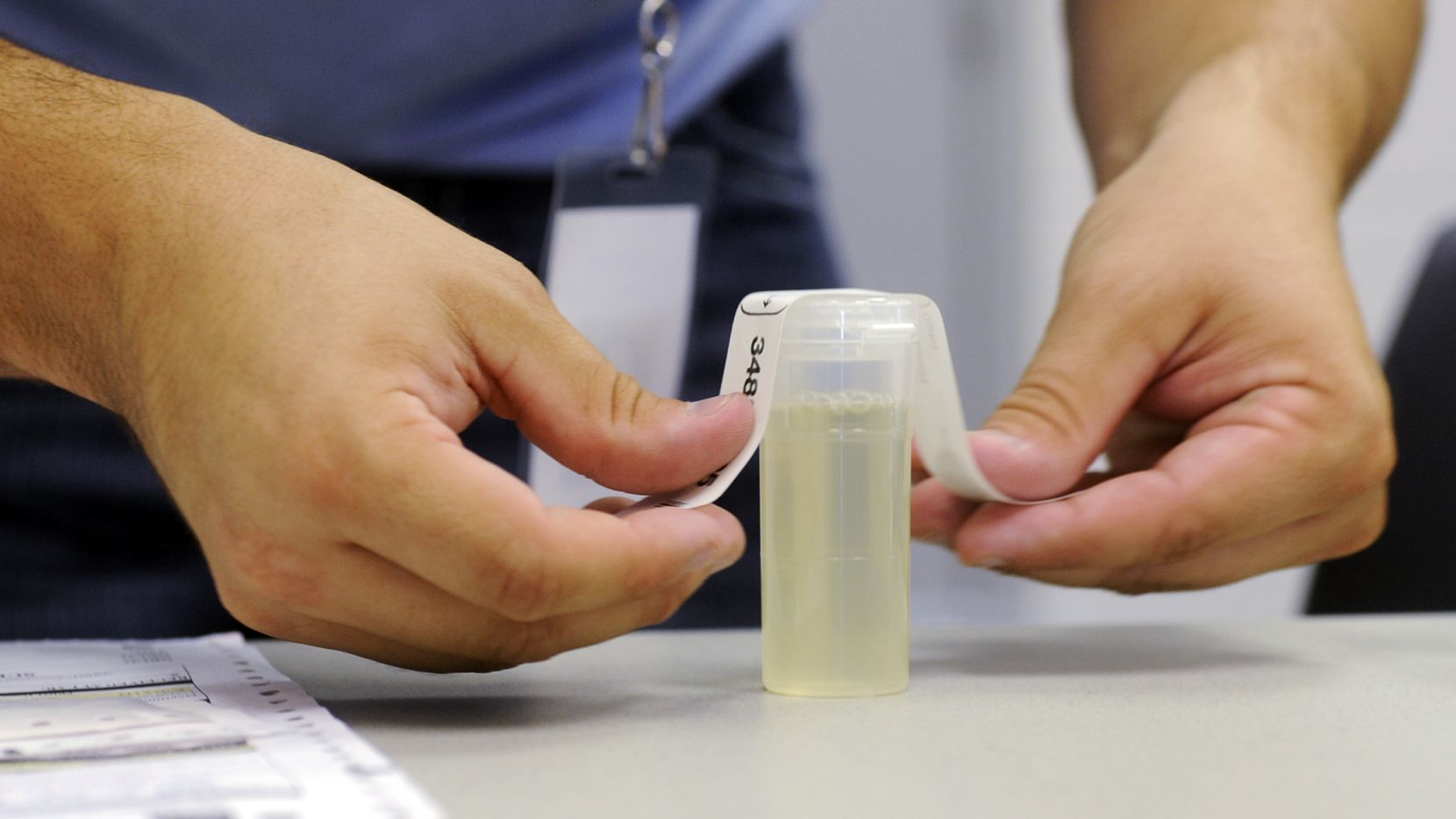 A worker labels a urine specimen vile in September 2011, at Linn State Technical College in Linn, Mo. (AP Photo/Kelley McCall)