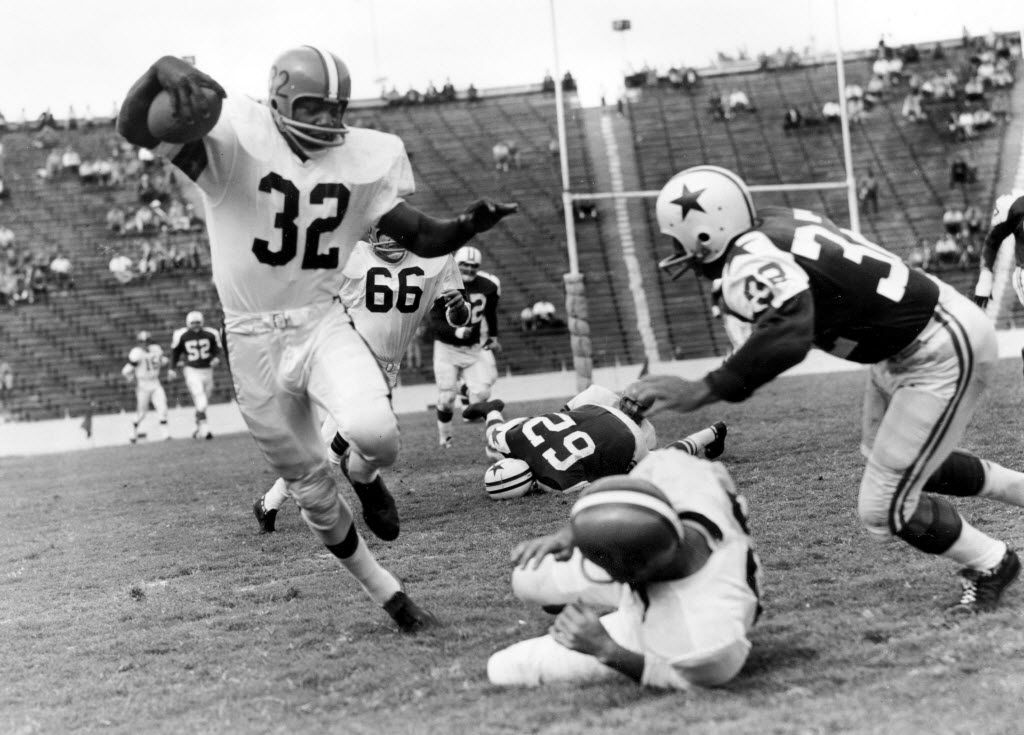 Jim Brown (32), fullback of the Cleveland Browns, rounds at right end after receiving a pass in the second quarter of their game in the Cotton Bowl and picks up yardage for a first down before he is brought down by Tom Franckhauser (32), Dallas Cowboys back.