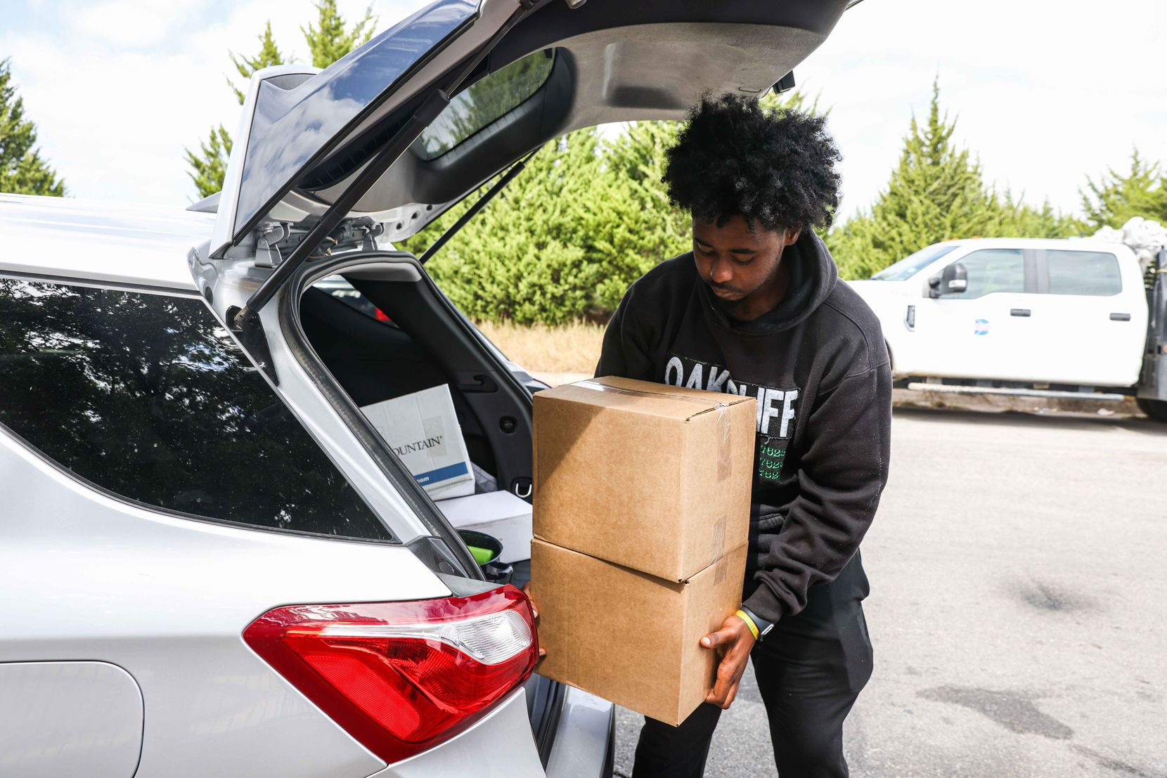Michael Berry, a program associate at For Oak Cliff, a nonprofit service agency, brings boxes of goods for residents displaced by Wednesday's explosion and fire.
