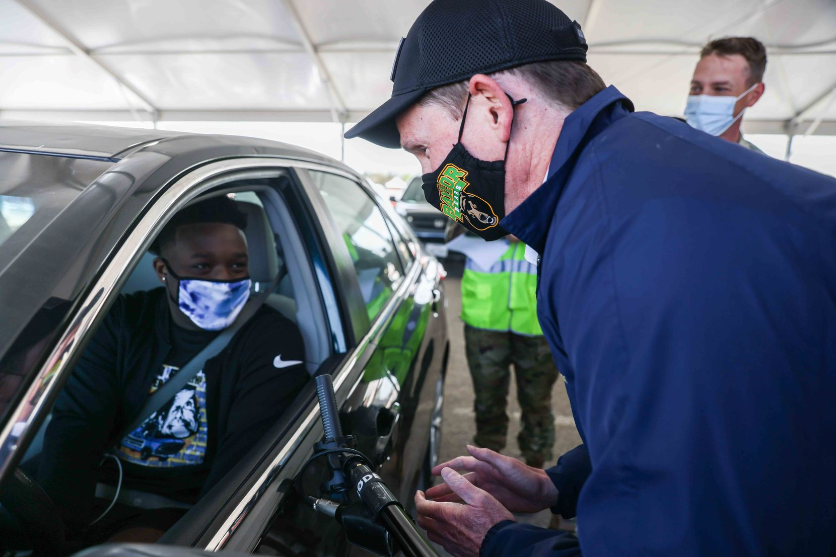 Dallas County Judge Clay Jenkins talked to Quincy Williams, 20, before he received the 250,000th vaccine provided by Dallas County at Fair Park.