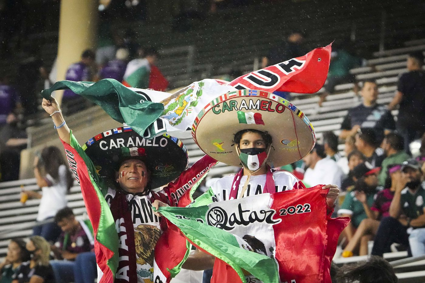 Mexico supporters cheer as rain falls on the stadium before a CONCACAF Gold Cup Group A soccer match against Guatemala at the Cotton Bowl on Wednesday, July 14, 2021, in Dallas. The start of the game was delayed due to weather.