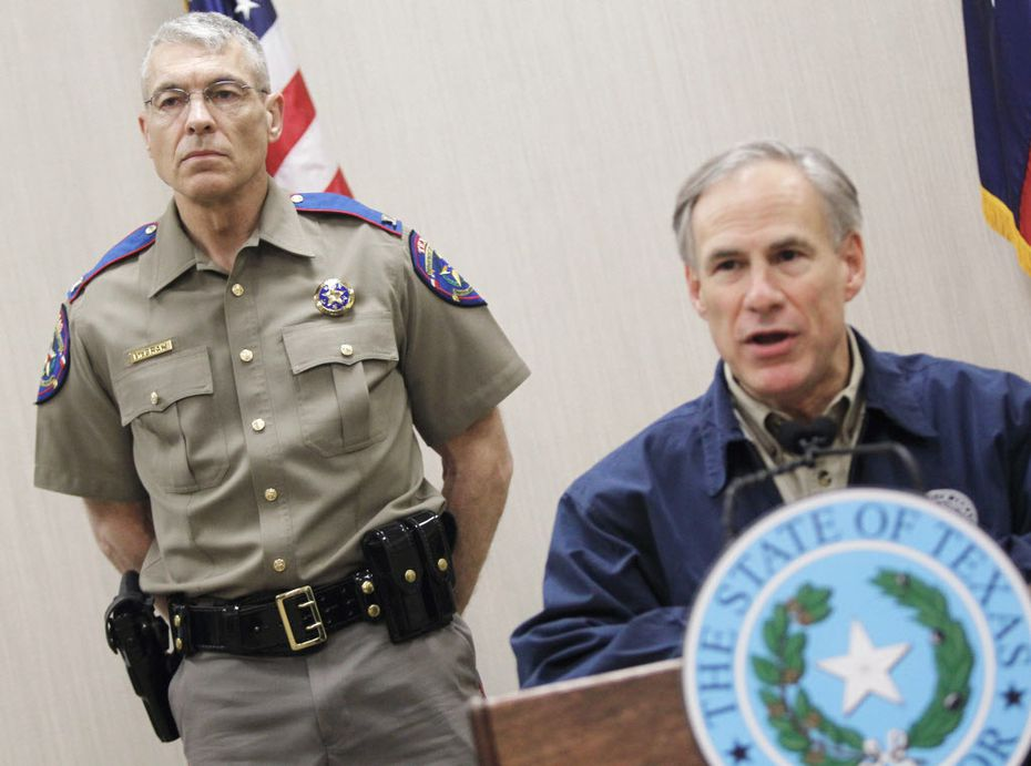 Texas Department of Public Safety Director Steve McCraw stands behind Gov. Greg Abbott. The two say they intend to funnel more money into the state's eight surveillance centers, called fusion centers, to help stop crime. (Nathan Lambrecht/The Associated Press)
