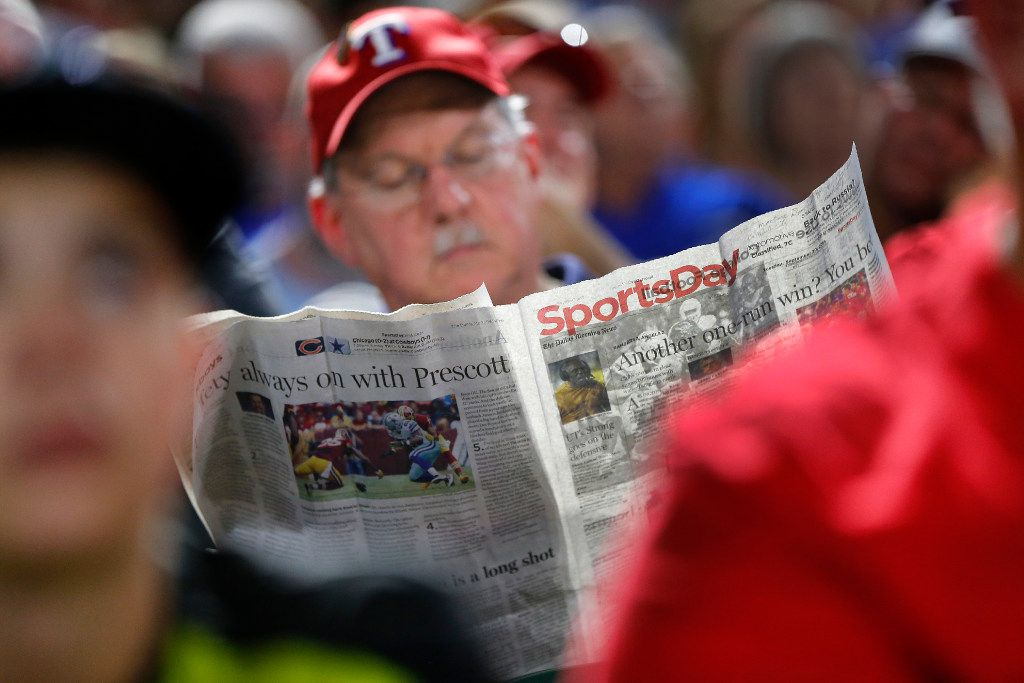 A Texas Rangers fan reads Sportsday section of the newspaper during the fifth inning of the Rangers Los Angeles Angels game at Globe Life Park in Arlington, Tuesday, September 19, 2016. (Tom Fox/The Dallas Morning News)