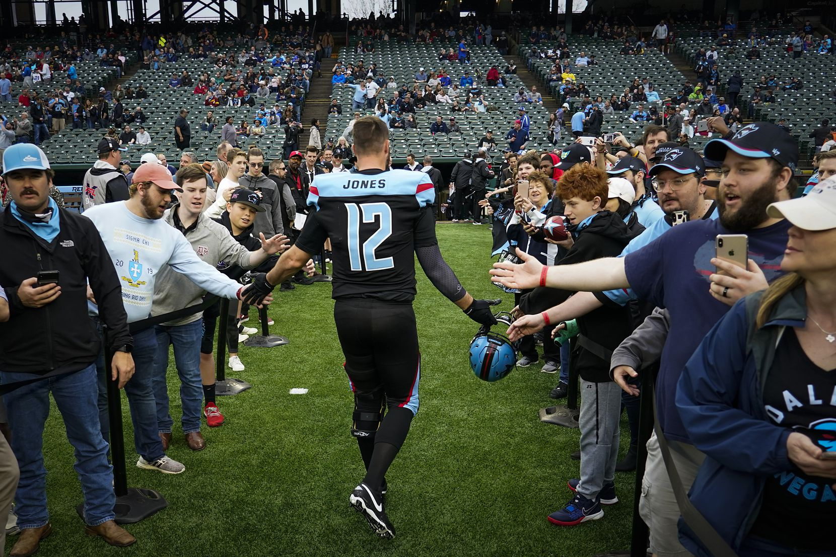 Dallas Renegades quarterback Landry Jones (12) high fives fans before an XFL football game against the St. Louis Battlehawks at Globe Life Park on Sunday, Feb. 9, 2020, in Arlington.