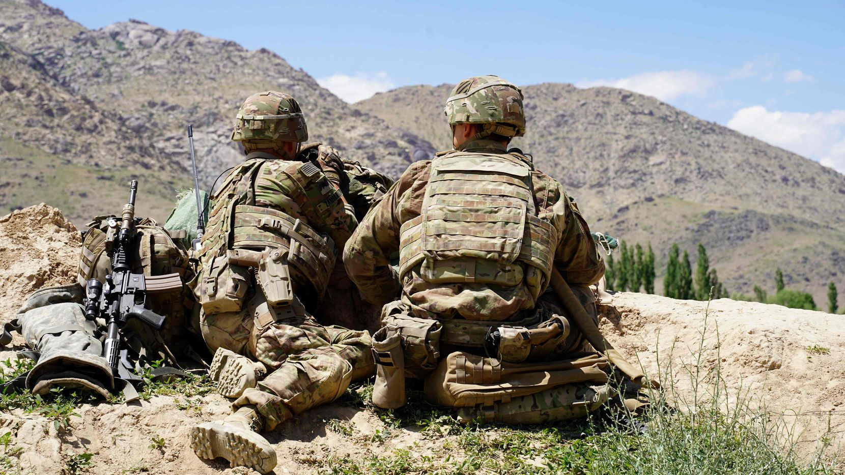 In this June 6, 2019, photo US soldiers look out over hillsides during a visit of the commander of US and NATO forces in Afghanistan Gen. Scott Miller at the Afghan National Army (ANA) checkpoint in Nerkh district of Wardak province. President Donald Trump denied on June 28, 2020, being briefed on intelligence that reportedly showed Russia had offered bounties to Taliban-linked militants for killing US soldiers in Afghanistan.