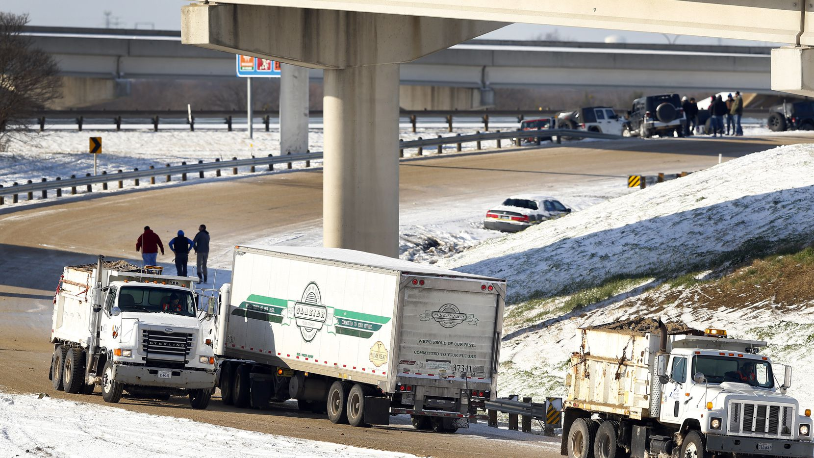 On a snowy day in March 2015, Texas Department of Transportation sanding trucks lay down a fresh coat of sand on the exit ramp from southbound SH 360 in Arlington.