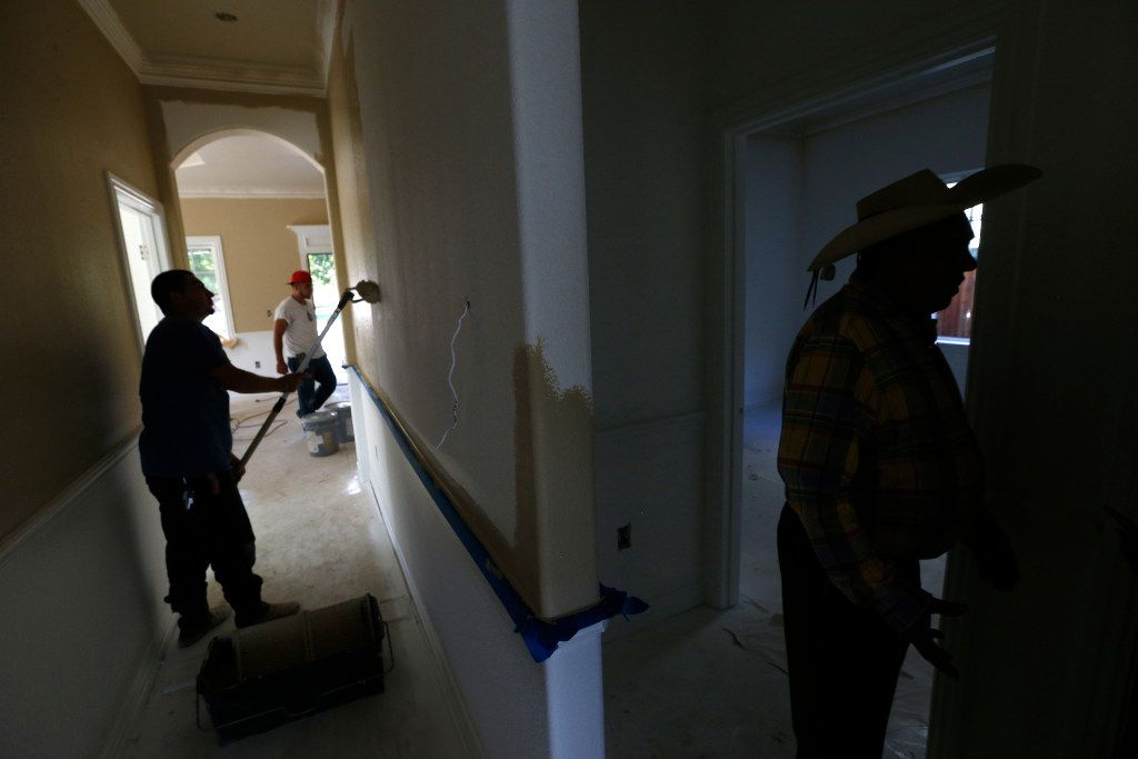 Santos Coria (right) gives a tour of one of his houses in the West Dallas neighborhood of Dallas as workers paint on Oct. 7, 2016.  (Nathan Hunsinger/The Dallas Morning News)