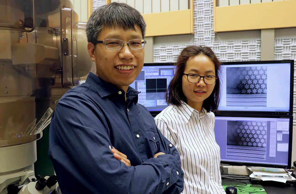 Qingxiao Wang (left) and Hui Zhu, both graduate students in materials science and engineering at The University of Texas at Dallas, used a transmission electron microscope to observe an unexpected phenomenon on the atomic scale (shown on the computer screens) in a material that might be suitable to power next-generation electronics. (UT-Dallas)