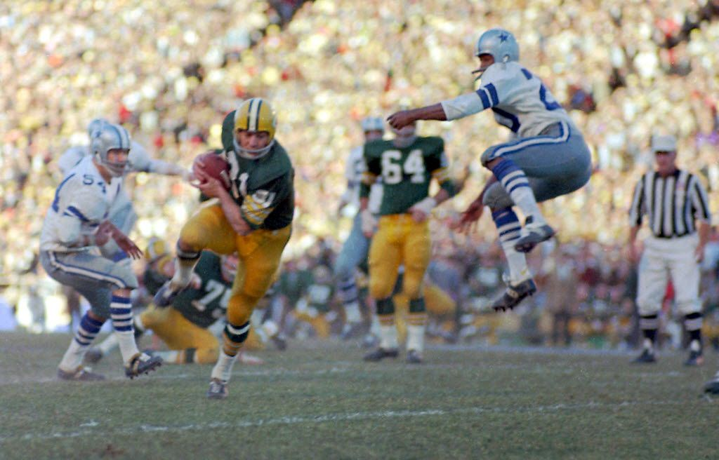 Green Bay Packers Jim Taylor runs with a Bart Starr pass as the Dallas Cowboys' Mel Renfro (20) leaps too late to break up the pass during the NFL Championship game, Jan. 1, 1967 in  Dallas.  At left is Cowboys Chuck Howley (54).