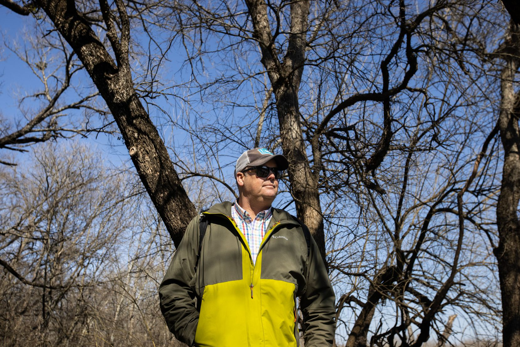 "Texas master naturalist Ben Sandifer stands under a canopy of dormant trees in the Great Trinity Forest, ""Before we start considering ripping out any part of the forest,"" Sandifer said, ""let's think about whether we will cause more harm than the ash borer."""