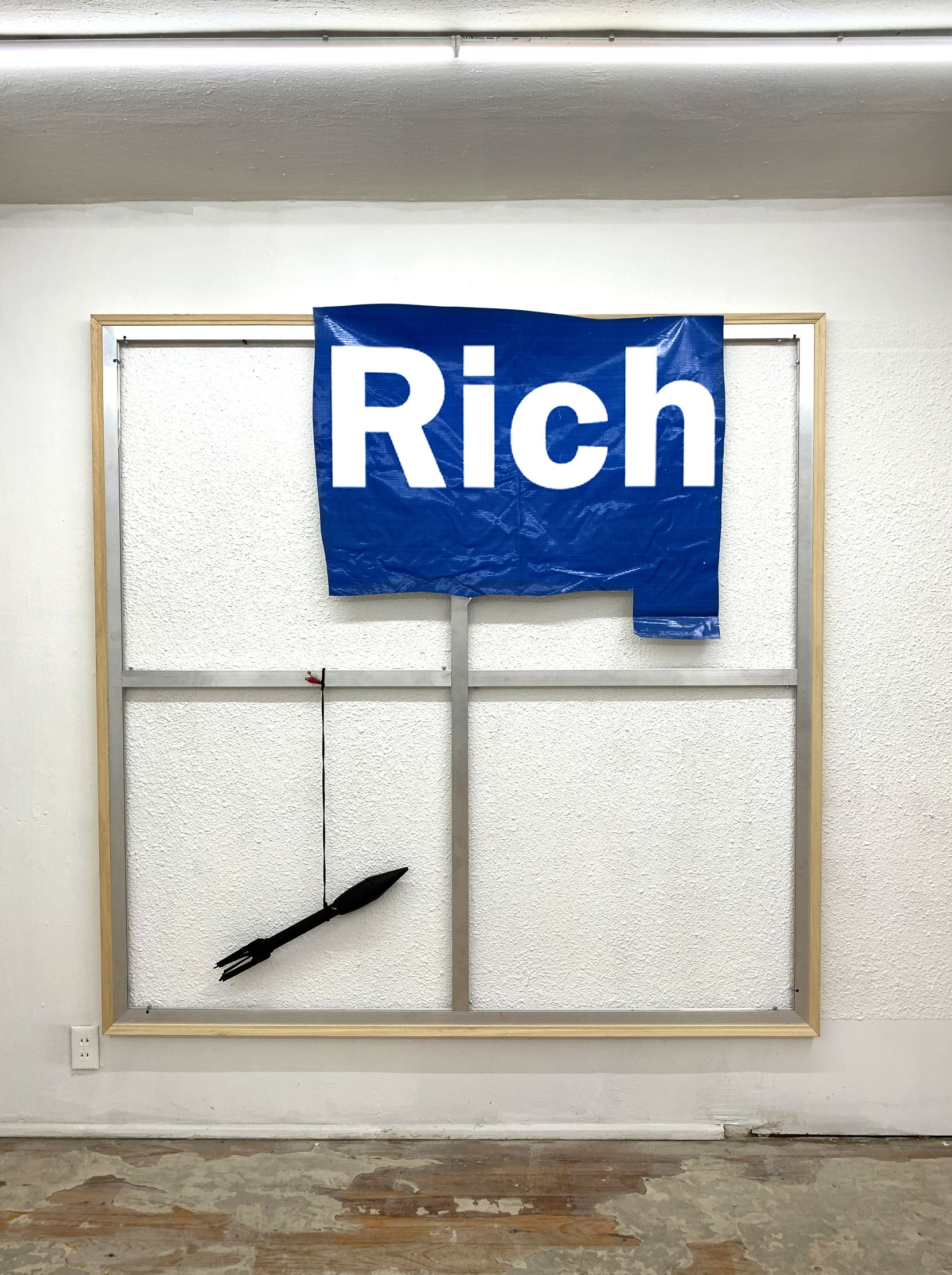 """Mark Flood's """"Rich"""" (2020), vinyl on aluminum and wood stretcher bar, with dummy munition and electronic wire, is on display through July 31."""