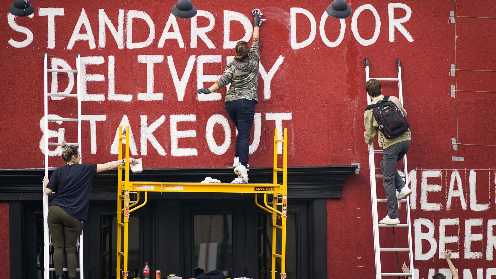 "From left, Sarah Schwartz, a server at sister property Clover, Xochitl Moctezuma, the wife of a kitchen staff member at The Standard Pour, and Jeffery Hook, the manager at Clover, paint signage advertising takeout and delivery covering the entire front wall at The Standard Pour in Uptown on Tuesday, March 17, 2020, in Dallas. After the city closed bars and limited restaurants to takeout, delivery and drive-thru only in response to the new coronavirus, owner Eddie ÔLuckyÕ Campbell made the decision to combine the staffs of The Standard Pour and sister bars Clover and Parliament into one delivery and takeout operation. Server Bre Archuleta said that while the effort to reinvent the bar and restaurant was intended to help the neighborhood and the community, she and the rest of the staff appreciated that Campbell was doing this also, ""so we all still have jobs.  He wanted to take care of us all as a family.""  While watching the staff paint Campbell said, ""this may be the most American thing I've ever done."""