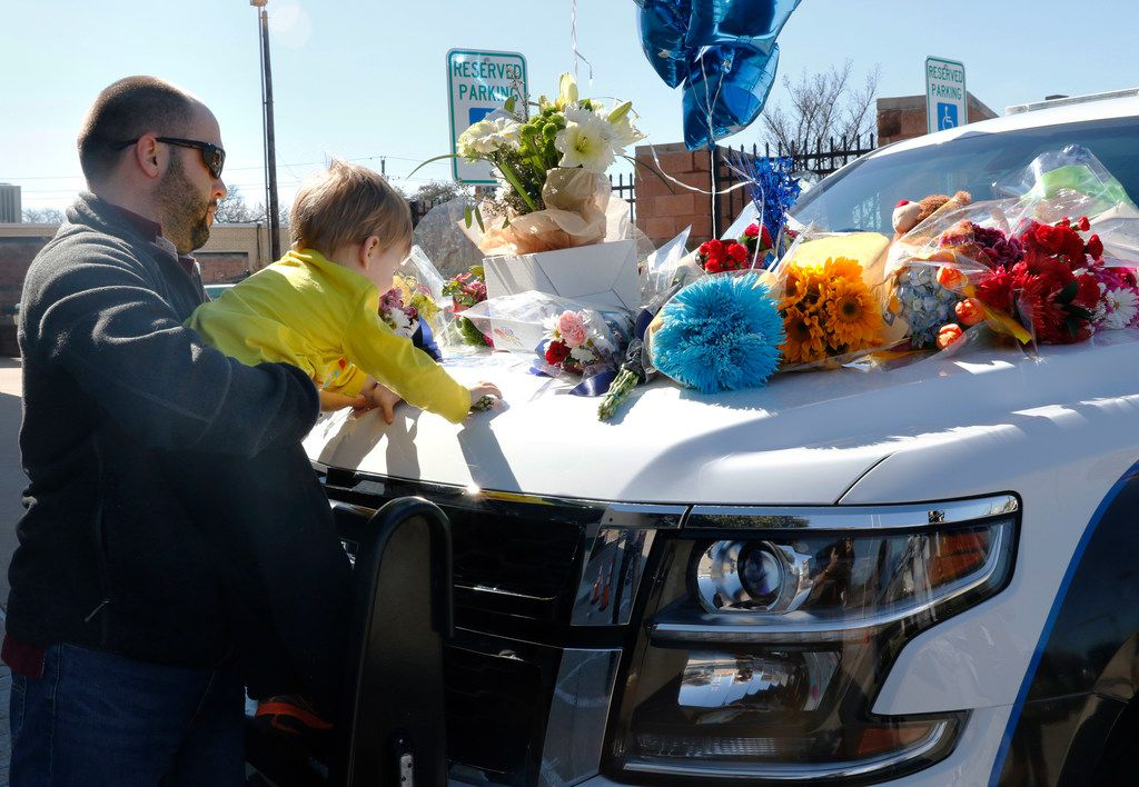 Kevin Goldsmith holds his son Henry, 2, of Richardson as he places flowers on the police cruiser at the Richardson, Texas police headquarters on Thursday, Feb. 8, 2018. A Richardson police officer was fatally shot the night before at an apartment complex.