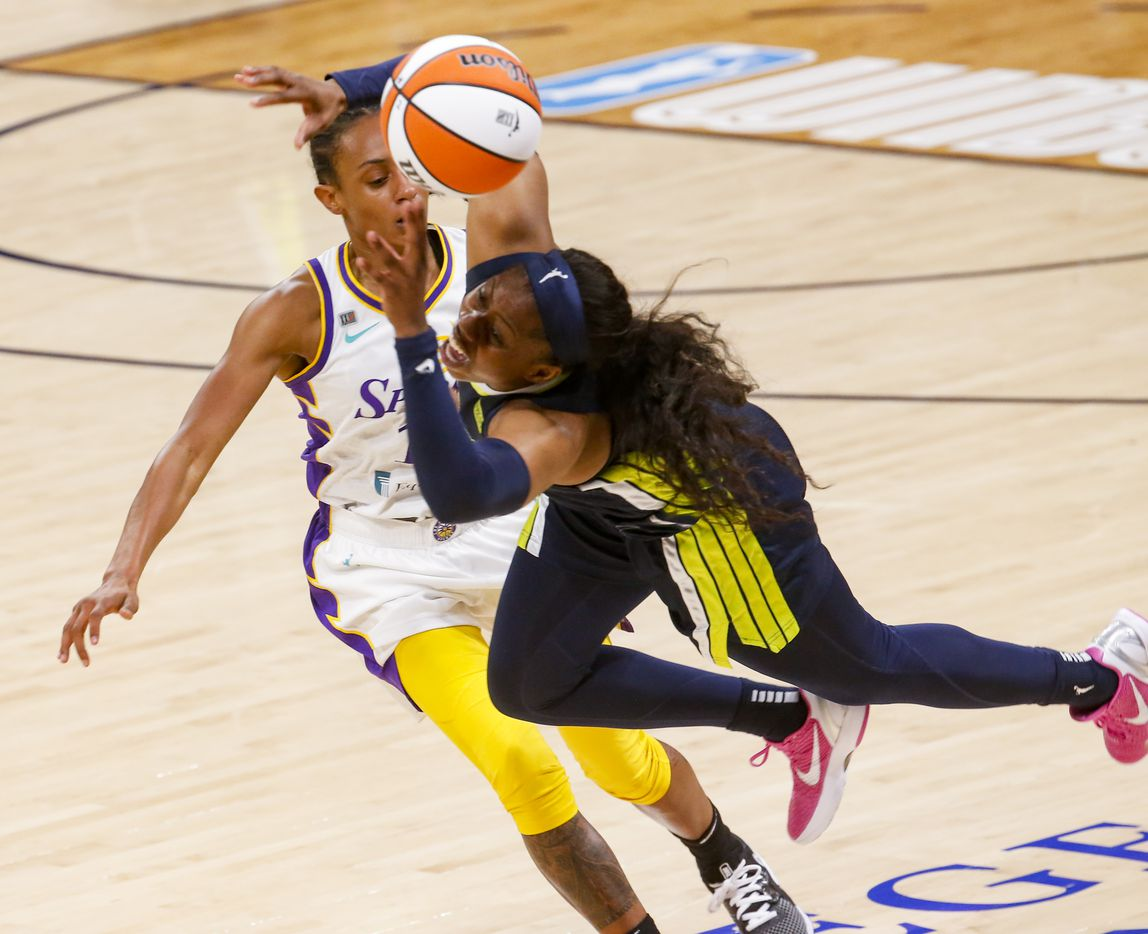 Dallas Wings guard Arike Ogunbowale (24) trips over Los Angeles Sparks guard Brittney Sykes (15) during the fourth quarter at College Park Center on Tuesday, June 1, 2021, in Arlington. (Juan Figueroa/The Dallas Morning News)