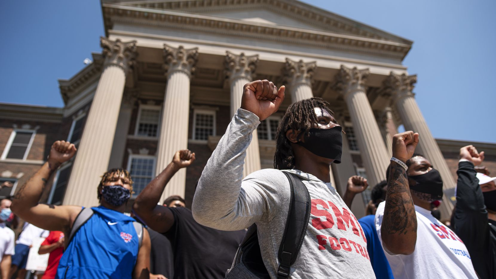 SMU football player Brandon Crossley, center, puts his fist in the air with other Black student athletes as they chant outside of Dallas Hall during a Black Lives Matter movement march on the campus in Dallas, Aug. 28, 2020. (Ben Torres/Special Contributor)