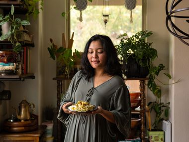 May Naing holds a plate of Nan Gyi Thoke, a popular dry noodle dish in Myanmar, in her home in Garland.