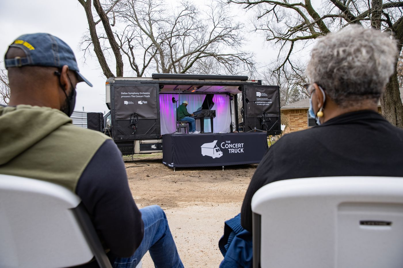 Marsha Jackson (right) and first cousin Shawn Williams listen to Shaun Martin perform outside of Jackson's home in Dallas on Friday, Feb. 26, 2021. Quincy Roberts, the contractor who moved Shingle Mountain, surprised Jackson with the concert. (Juan Figueroa/ The Dallas Morning News)