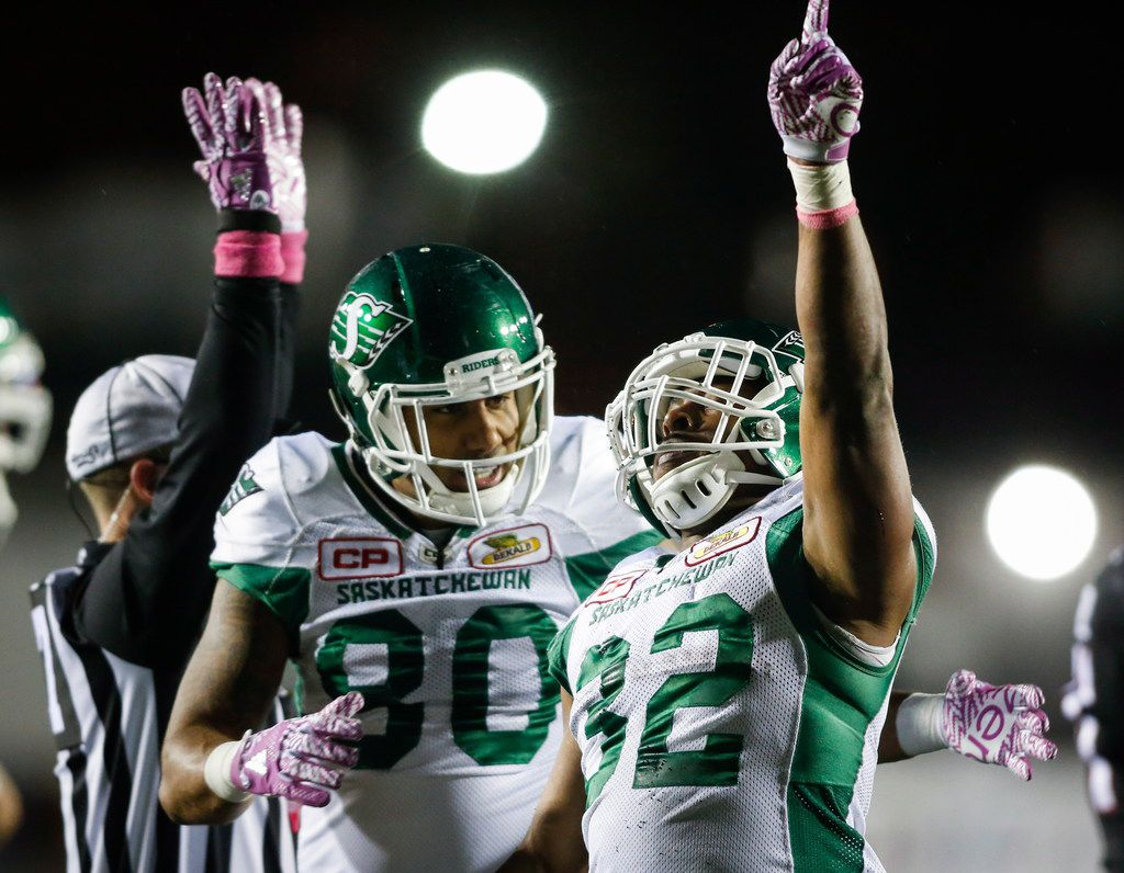 Saskatchewan Roughriders' Cameron Marshall (right) celebrates a touchdown with Spencer Moore against the Calgary Stampeders during the second half of a Canadian Football League game in October.
