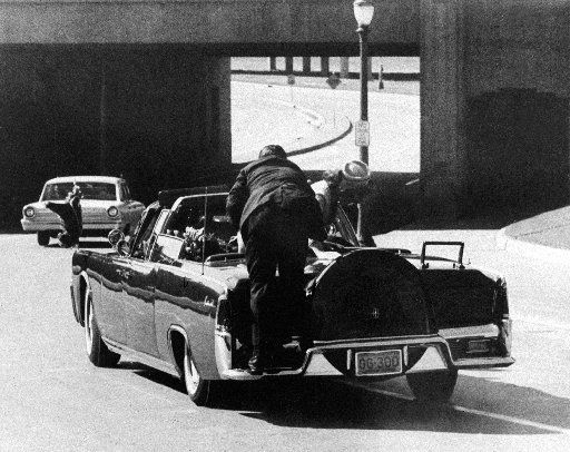 President Kennedy slumps down in the back seat of the limo after being shot in Dallas on Nov. 22, 1963. Jacqueline Kennedy leans over the president as Secret Service agent Clinton Hill rides on the back of the car.