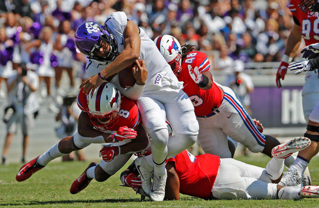 TCU Horned Frogs quarterback Kenny Hill (7) gets hit by SMU defenders while running the ball in the first quarter as TCU beats SMU 56-36 in their annual Iron Skillet game in Fort Worth, Saturday, September 16, 2017. ORG XMIT: B7310934504Z.1