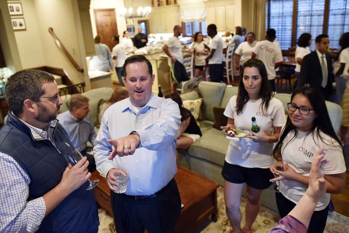 Dustin Marshall points at early results while speaking with campaign volunteers Camila Correa and Azhalia Leal early on during the election watch party at his home.