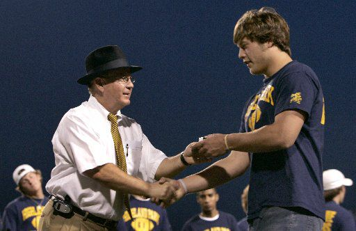 Highland Park football head coach Randy Allen presents quarterback Matthew Stafford with his championship ring at a ceremony Saturday night, April 1, 2006, at Highlander Stadium in Dallas, Texas.