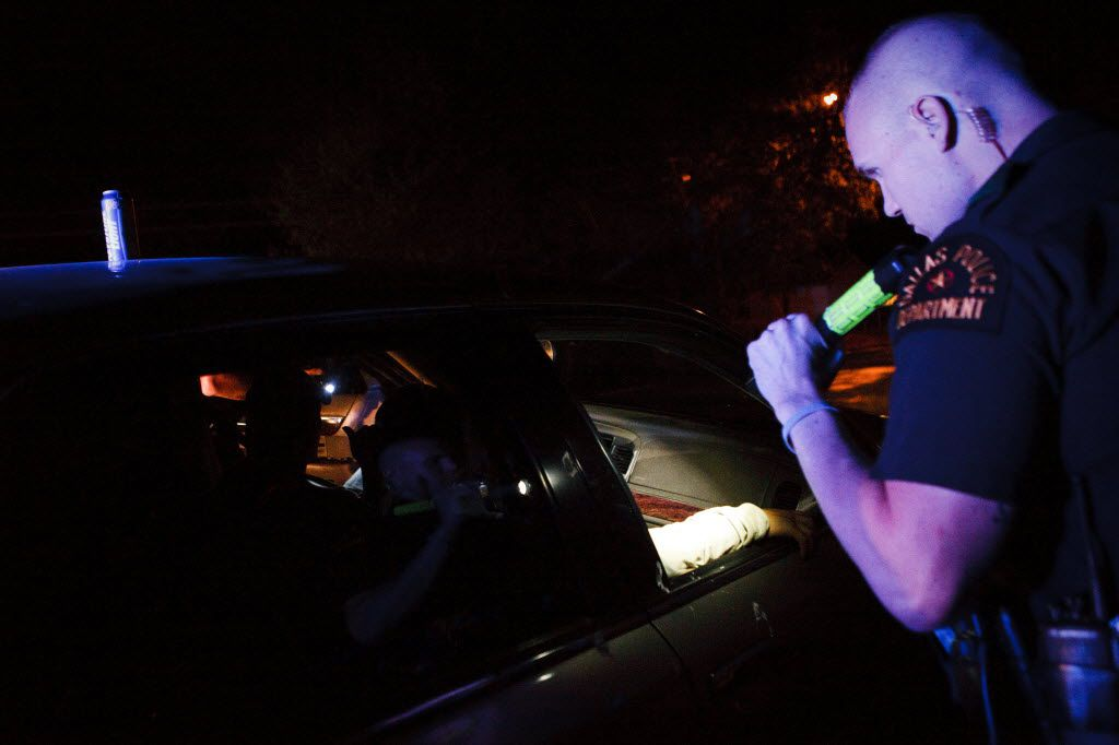 Dallas police Officer Bryan Burgess shines his flashlight into a car before arresting the occupants for outstanding warrants in the Pleasant Grove area. (2011 File Photo/Staff)